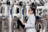 vonzó mérnök fehér kabátban és szemüvegben tartja fekete mappa közelében levegő sűrített rendszer