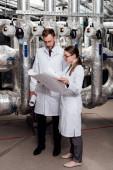 szemüveges és fehér köpenyes mérnökök, akik a légkompresszor-rendszer melletti tervrajzot nézik