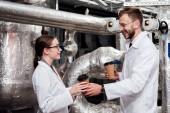 Fotografie fröhlicher Ingenieur mit Pappbechern in der Nähe glücklicher Mitarbeiter