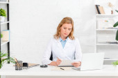 attractive nutritionist sitting at table and writing on paper in clinic