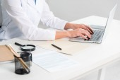cropped view of nutritionist sitting at table and using laptop in clinic
