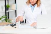 ořezaný pohled na odborníka na výživu sedícího u stolu a razítkujícího papír na klinice
