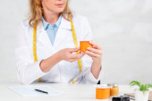 cropped view of nutritionist sitting at table and holding yogurt in clinic