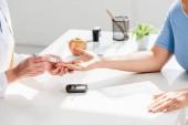 Fotografie ostříhaný pohled na odborníka na výživu sedícího u stolu a provádějícího krevní testy od pacienta na klinice