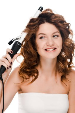 happy girl looking away while curling hair isolated on white