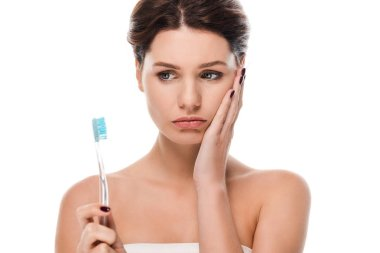 sad young woman touching face while holding toothbrush isolated on white