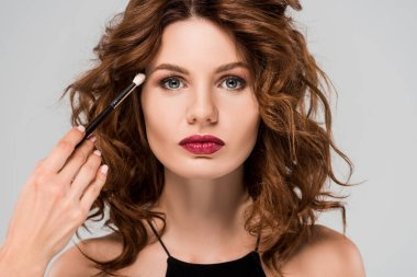 cropped view of makeup artist apply eye shadow on young curly woman isolated on grey