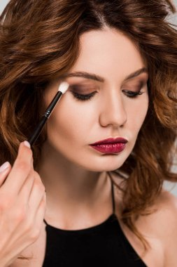 cropped view of makeup artist apply eye shadow on beautiful woman isolated on grey