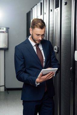 Businessman in suit using digital tablet in data center stock vector