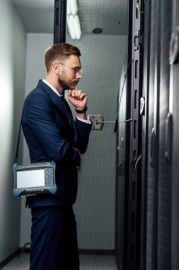 Side view of pensive businessman standing with reflectometer in server room stock vector