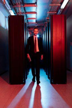 Bearded businessman in glasses holding digital tablet and walking in server room stock vector
