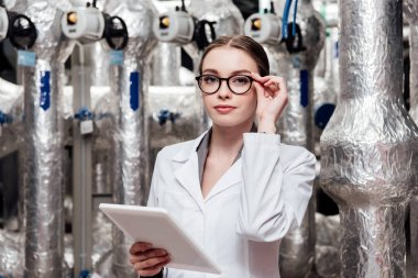 attractive engineer in white coat touching glasses while holding digital tablet near air compressed system