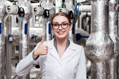 Happy engineer in white coat and glasses showing thumb up near air compressed system stock vector