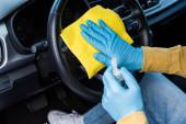 abgeschnittene Ansicht eines Mannes in Latexhandschuhen mit antiseptischen Mitteln und Lappen zur Reinigung des Autoinnenraums während der Coronavirus-Pandemie
