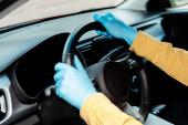 Fotografie oříznutý pohled řidiče v ochranných rukavicích držících volant během pandemie covid-19