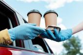 Fotografie abgeschnittene Ansicht eines Mannes in Schutzhandschuhen, der während der Coronavirus-Pandemie Kaffee zum Mitnehmen aus dem Auto kauft