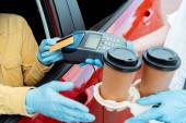 Fotografie abgeschnittene Ansicht eines Mannes in Schutzhandschuhen, der während der Covid-19-Pandemie Transaktion mit Kreditkarte und Terminal tätigt, um Kaffee zum Mitnehmen aus dem Auto zu kaufen