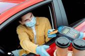 Fotografie Mann in medizinischer Maske tätigt Transaktion mit Kreditkarte und Terminal, um während der Coronavirus-Pandemie Kaffee zum Mitnehmen aus dem Auto zu kaufen