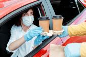 Fotografie Frau in medizinischer Maske und Handschuhen kauft Kaffee, um während der Coronavirus-Pandemie aus dem Auto zu gehen