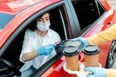 Fotografie Frau in medizinischer Maske und Handschuhen tätigt Transaktion mit Kreditkarte und Terminal, um während der Covid-19-Pandemie Kaffee zum Mitnehmen aus dem Auto zu kaufen
