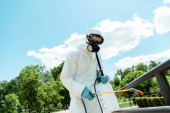 Photo specialist in hazmat suit and respirator disinfecting railings in park during covid-19 pandemic