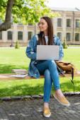 atraktivní student sedí na lavičce a pomocí notebooku v blízkosti knih, on-line studijní koncept