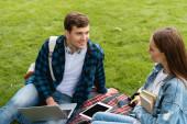 šťastný student při pohledu na atraktivní dívku v blízkosti gadgets na kostkované přikrývky
