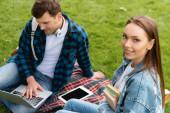 selektivní zaměření atraktivní dívky s úsměvem v blízkosti studenta pomocí notebooku, on-line studijní koncept