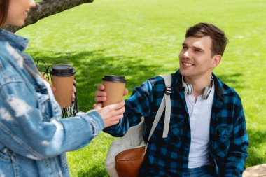 Selective focus of happy girl giving paper cup with coffee to handsome friend stock vector