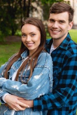 Cheerful student hugging attractive girlfriend in denim jacket stock vector