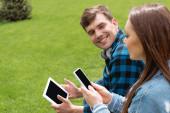 selektivní zaměření veselého studenta při pohledu na dívku s chytrým telefonem, zatímco drží digitální tablet s prázdnou obrazovkou