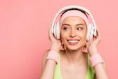 veselá žena dotýkající se sluchátek při poslechu hudby izolované na růžové