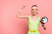 Photo cheerful young woman with clenched fist holding loudspeaker on pink