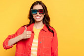 happy young woman in 3d glasses showing thumb up isolated on yellow