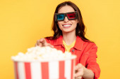selective focus of happy young woman in 3d glasses reaching popcorn isolated on yellow