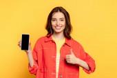 glückliche junge Frau hält Smartphone mit leerem Bildschirm und zeigt Daumen hoch auf gelb