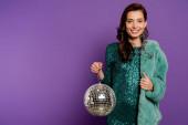 vidám és elegáns nő kezében disco labda és mutatja hüvelykujját fel a lila