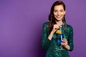 fröhliche Frau im Partykleid mit Alkoholcocktail und Stroh auf lila
