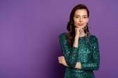 Fotografie atraktivní mladá žena v šatech dotýkající se obličeje a při pohledu na kameru na fialové