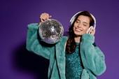 vidám nő megható fejhallgató és tartsa disco labda lila