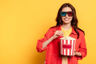 Cheerful young woman in 3d glasses holding popcorn bucket on yellow stock vector