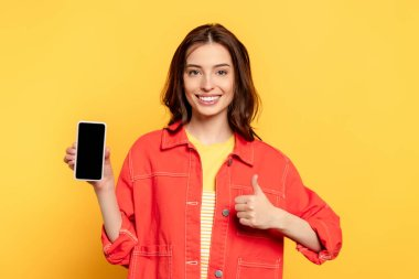 Happy young woman holding smartphone with blank screen and showing thumb up on yellow stock vector