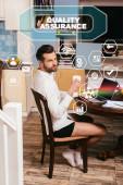 Selektivní zaměření pohledného muže v košili a kalhotkách pomocí notebooku a podpažního šálku v obývacím pokoji, ilustrace zajištění kvality