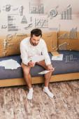 Freelancer v kalhotkách a košili při pohledu na dokumenty s grafy na pohovce, grafy a grafy ilustrace