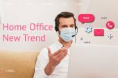 Fotografie Selektive Fokussierung des Freiberuflers in medizinischer Maske mittels Headset beim Videoanruf am Laptop, Home Office neue Trendillustration