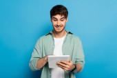 šťastný mladý muž pomocí digitální tablet na modré