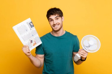 Happy young man holding newspaper and electric fan on yellow stock vector