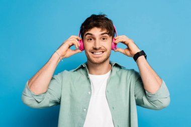 happy young man touching wireless headphones while listening music on blue