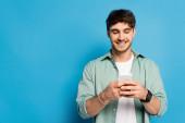 veselý mladý muž chatování na smartphone na modré