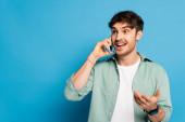 vidám fiatalember beszél okostelefonon, miközben áll tárt karokkal kék